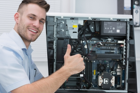 Portrait of young hardware professional gesturing thumbs up by an open cpu photo