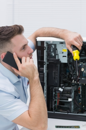 Side view of young computer engineer working on cpu while on call at workplace photo
