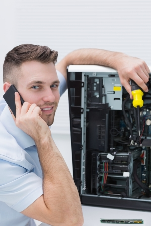 Portrait of young computer engineer working on cpu while on call at workplace Stock Photo - 18108389