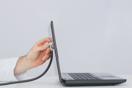 Close-up of hand examining laptop with stethoscope against plain background