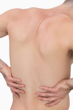 Rear view of muscular man with backache over white background photo