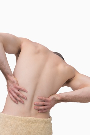 Rear view of shirtless man with back pain over white background photo