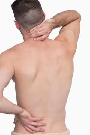 back sprains: Rear view of shirtless man with neck pain over white background Stock Photo