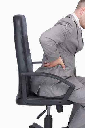 lower back pain: Side view of business man with backache sitting in an office chair over white background