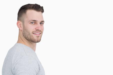visage homme: Portrait vue de côté de jeune homme souriant sur fond blanc