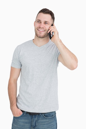 Casual young man using mobile phone over white background photo