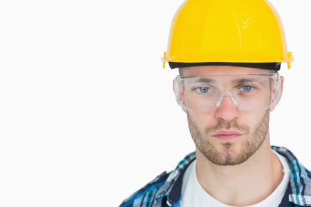 Close-up portrait of architect wearing protective eyewear and hardhat over white background photo