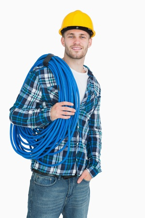 coiled: Portrait of smiling young male architect carrying coiled blue tubing over white background
