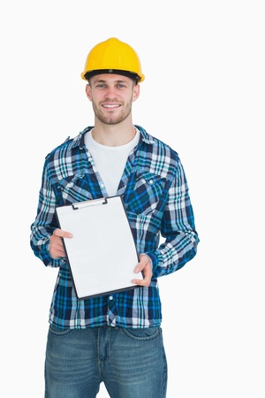 Portrait of smiling young male architect holding clipboard over white background photo