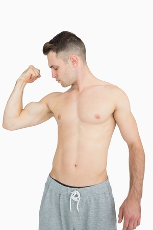 Shirtless young man flexing muscles over white background photo