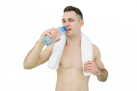 Portrait of young man drinking water with towel around neck over white background photo