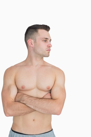 bare chested: Bare chested young man with arms crossed looking to his side over white background