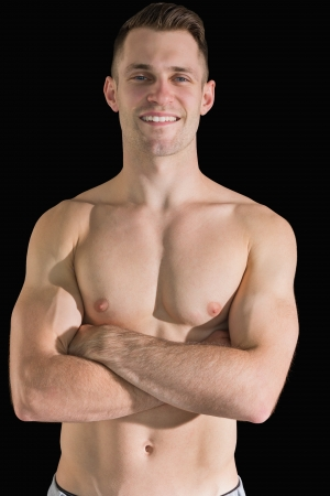 male chest: Portrait of bare chested young man with arms crossed over black background