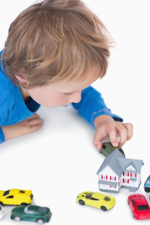 Close-up of boy playing with playhouse and toy cars over white background photo