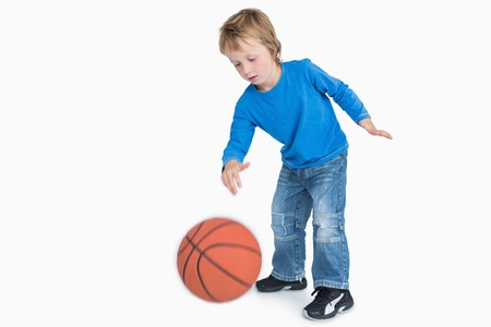 Young casual boy playing basketball over white background