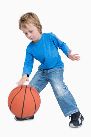 dribbling: Young casual boy playing basketball over white background
