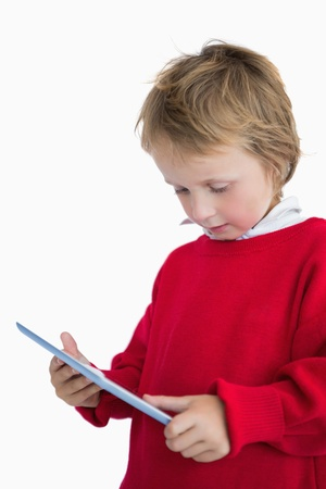 Little boy looking at digital tablet over white background photo