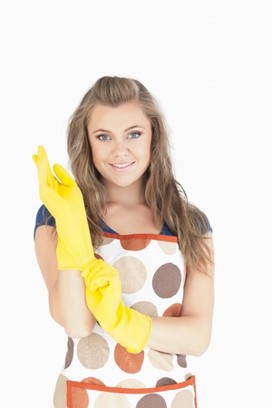 Portrait of beautiful young maid with rubber gloves over white background photo