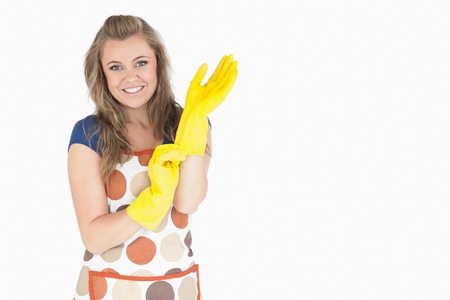 Portrait of smiling young maid with rubber gloves over white background photo