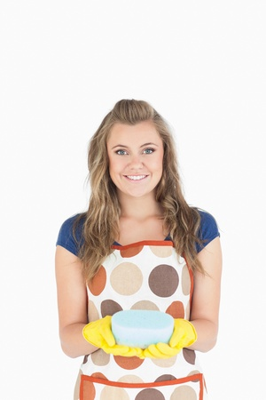Portrait of smiling young maid holding sponge over white background Stock Photo - 18107037