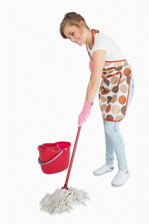 Young maid mopping floor over white background photo