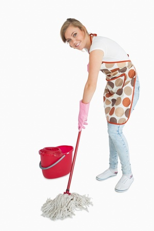 Portrait of young maid mopping floor over white background photo