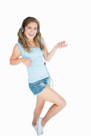 air guitar: Portrait of woman enjoying music over headphones and playing air guitar against white background
