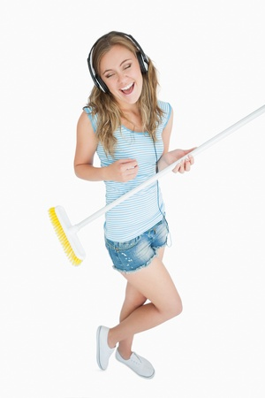 Woman playing air guitar with broom while listening music over headphones against white background photo