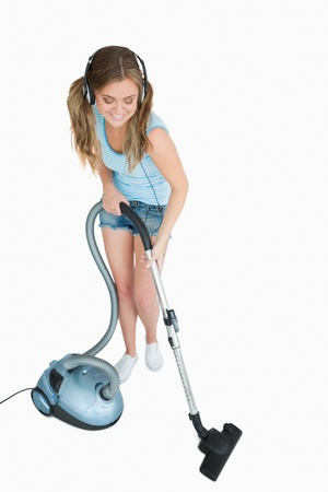 Young woman listening music over headphones while vacuuming against white background Stock Photo - 18102050