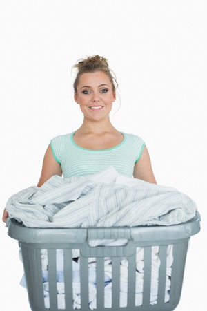 Portrait of smiling young woman carrying laundry basket over white background photo