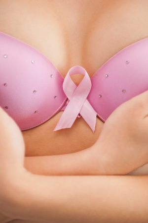 Close-up of woman in bra with breast cancer awareness ribbon photo