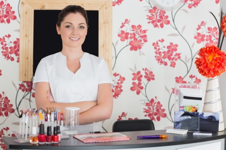 standing reception: Portrait of confident young woman with arms crossed at reception in nail salon Stock Photo