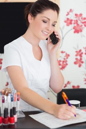 Young woman answering phone at reception of nail salon photo