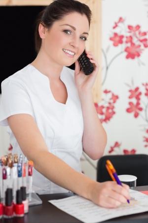 recepcionista: Retrato de mujer joven y contestar el tel�fono en la recepci�n del sal�n de belleza