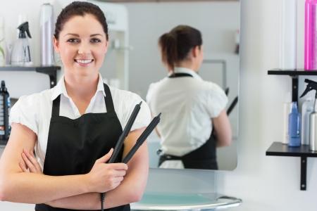 straightener: Portrait of female hairdresser holding hair straightener