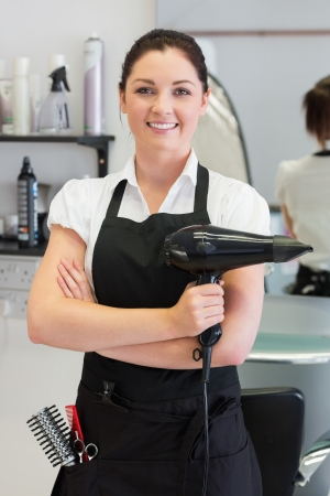 Portrait of confident female hairdresser holding hair dryer photo