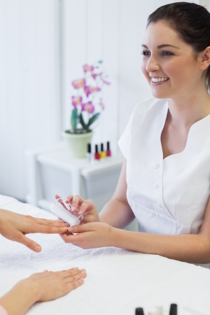 manicurist: Happy young manicurist using nail brush on womans nails