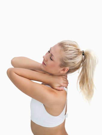 Side view of sporty young woman massaging neck over white background photo