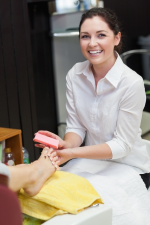 Portrait of young woman buffering toe nails at spa center Stock Photo - 18109046