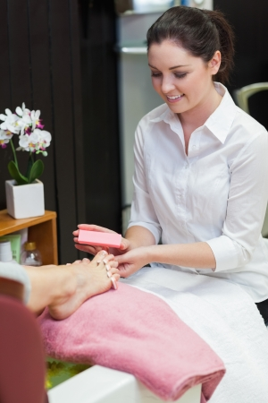Young woman buffering toe nails at spa center Stock Photo - 18109130