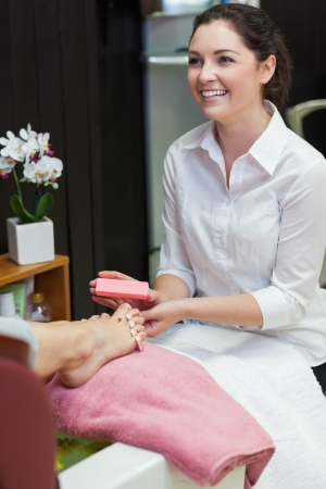 Young woman buffering toe nails at spa center photo