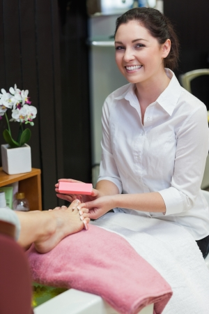 Portrait of young woman buffering toe nails at spa center photo