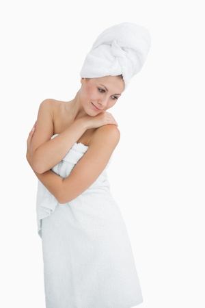 Happy young woman wrapped in towel over white background photo