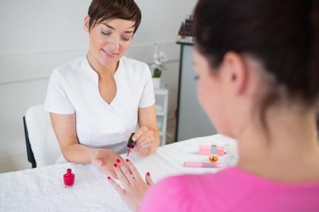 finger nails: Nail technician applying nail varnish to finger nails at nail salon Stock Photo