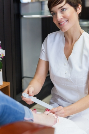 Nail technician filing woman's toe nails at nail salon Stock Photo - 18110524