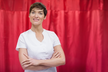 Portrait of a hairdresser with arms crossed against red curtain photo