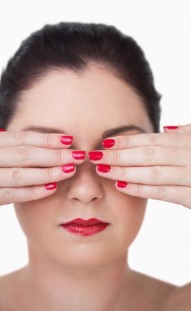 Mujer joven sensual que cubre los ojos con las u�as pintadas de color rojo sobre fondo blanco Foto de archivo - 18107443