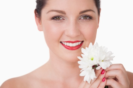 Close-up of young woman holding flower over white background photo