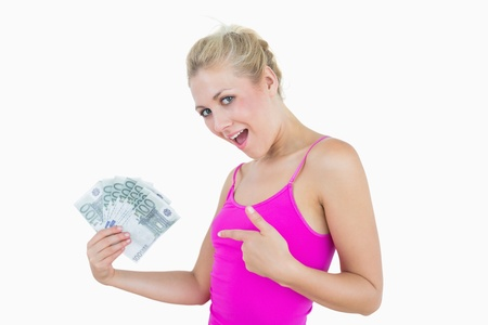 Portrait of happy woman pointing at fanned euro banknotes over white background photo