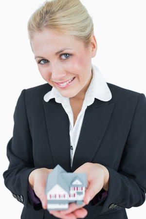 Portrait of young business woman holding model house over white background photo